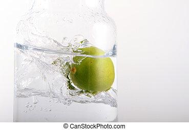 lemon falling into glass of water