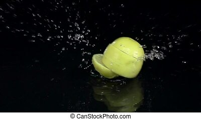 Lemon falls into the water and dissolves into slices. Black background. Slow motion