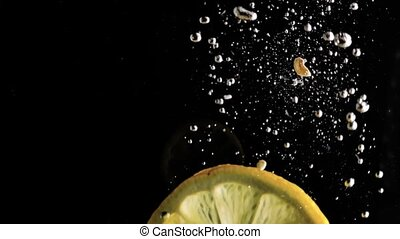 lemon falls into the water on a black background. slow motion