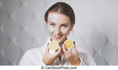 Lemon Fun and Face Mask - Fair hair girl having fun with two...