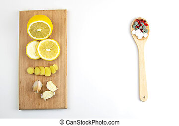 Lemon, ginger, and chapel against multi-colored tablets. The concept of choosing a healthy diet versus taking medication