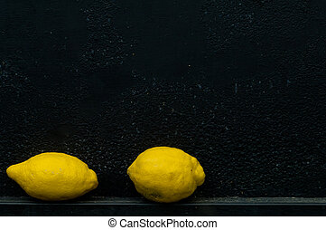 Lemon in front of rough textured black background