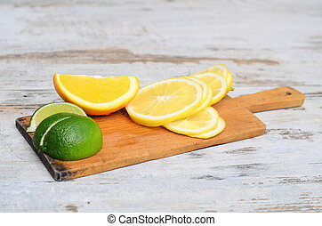 lemon, lime and tangerine on wooden cutting board