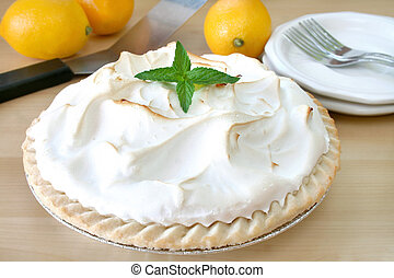 Close up of a lemon meringue pie garnished with fesh mint leaves.