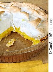 Home-baked lemon meringue pie, in brown pottery pie plate. One slice missing.