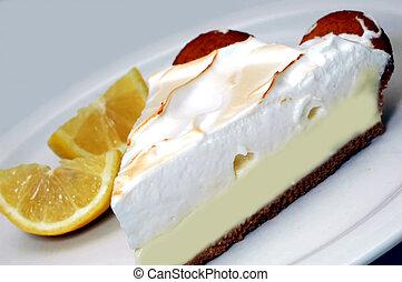 Lemon meringue pie with lemons in background.