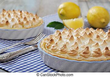 Lemon Meringue Pie with fresh lemons on checkered background
