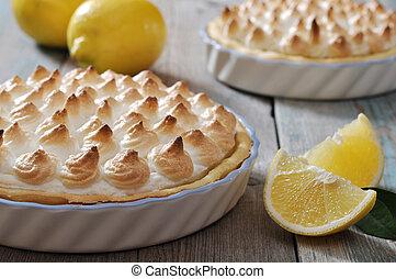 Lemon Meringue Pie with fresh lemons on wooden background