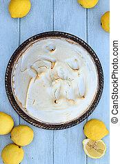 Lemon Meringue Pie with fresh lemons over a beautiful blue wooden background.