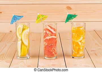 Lemon orange and grapefruit in glass on table.