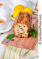 Lemon pound cake with dried cranberries and raisins on white wooden background