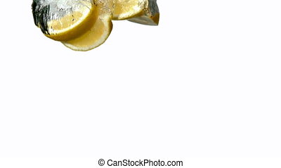 Lemon segments plunging into water on white background in...