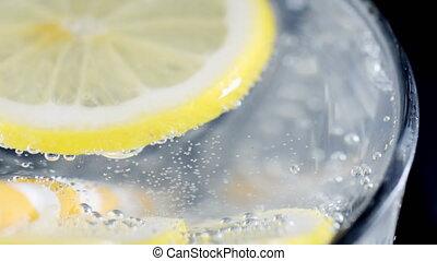 Lemon slice in soda water. - Slow motion shot of slice of...