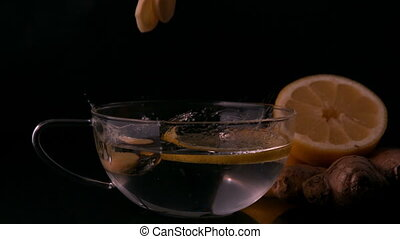 Lemon slices falling into glass cup