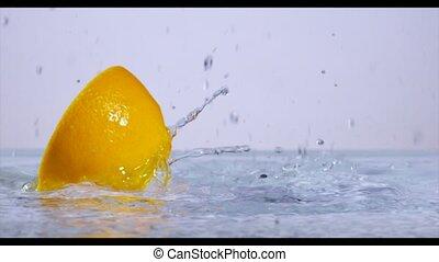 Lemon slices falling into water, slow motion. - Lemon slices...