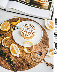 Lemon tart with merengue sweet dessert over white marble table in cafe. French cuisine, comfort food, fine dining concept
