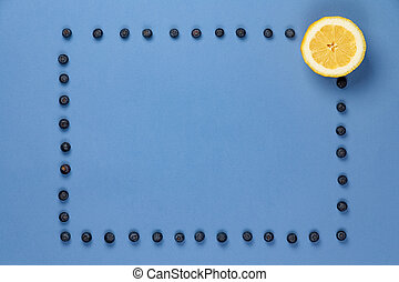 Lemon with frame of blueberries on a blue background.