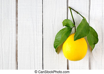 Lemon with leaves on wooden background