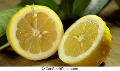 Lemon cut in half under water drops.