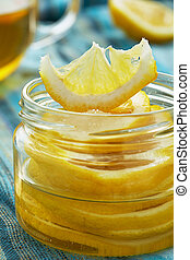 Lemon with sugar is in a glass jar