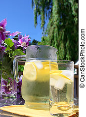 Lemonade in jar and glass with lemons, ice, on outdoor table...