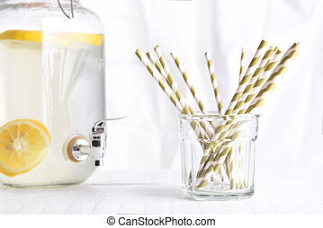 Lemonade pitcher with a glass of drinking straws