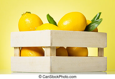 Lemons be in wooden box on yellow background