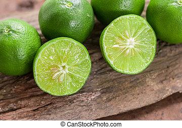 Lemons - Green lemons from the garden on wooden background, Select focus, Soft focus and blur