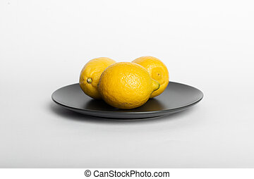 Lemons in a black saucer isolated on white background