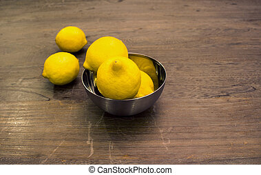 lemons in a metal bowl on wood table