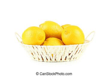 Lemons in basket isolated on white