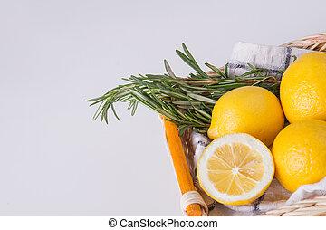 Lemons in basket with rosemary.