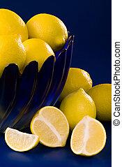 lemons in blue bowl on blue background
