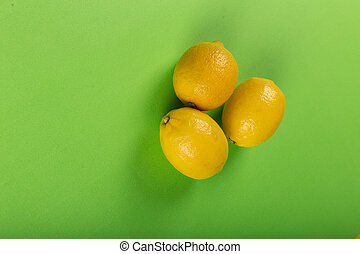 Lemons in the middle on a green backdrop