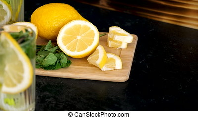 Lemons on a wooden board and two glasses with homemade...