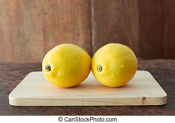 Lemons on a wooden plate - Close up fresh of lemons on a...