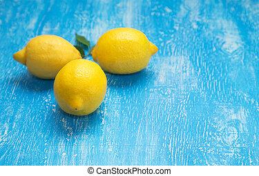 Lemons on blue wooden background.