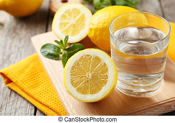 Lemons on cutting board with glass of water on grey wooden background