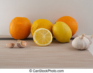 Lemons, oranges and garlic on a light background. Set of vitamins becouse of corona virus.