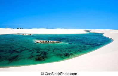 view of lagoa azul in desert white sand dunes of the Lencois Maranheses National Park in brazi