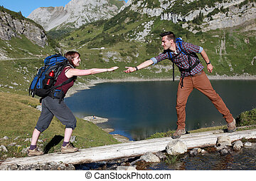 A young male hiker is helping a female hiker to cross a brook in the mountains