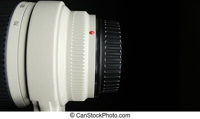 Lens cap with clipping path, on black - Hand puts and off a...