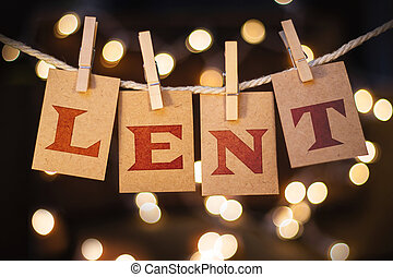 The word LENT printed on clothespin clipped cards in front of defocused glowing lights.