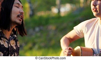 lent, dépenser, motion., deux, jeune, guitare, chant, hommes, dehors, week-end, jouer, sunset.