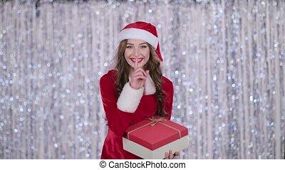 lent, elle, cadeau, quietly., mouvement, arrière-plan., bokeh, doigt, santa, mains, girl, spectacles, plus
