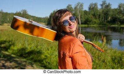lent, femme, stands, -, vacances, été, sourire, motion., elle, vacances, concept, shoulder., lunettes soleil, heureux, gens, nature, guitare