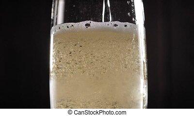 lent, gros plan, arrière-plan noir, verre, champagne, versé, motion.