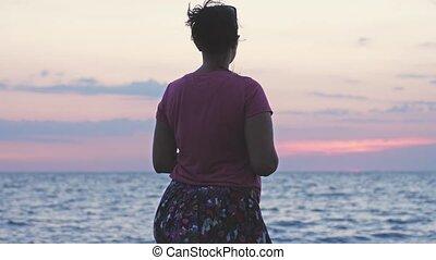 lent, rocheux, nature, motion., jeune femme, coucher soleil, pendant, apprécier, plage, stands