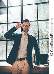lentes, oficina, alegre, café, casual, posición, el mirar joven, confiado, ventana, cámara, sonrisa, elegante, el suyo, grande, ajuste, uso, frente, hombre, mientras, businessman., o
