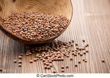 Lentils wooden bowl on wooden background. Healthy food.